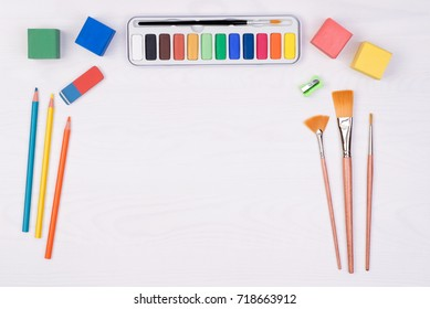 Kid's desk with colorful pencils, brushes and watercolors, top view with copy space
