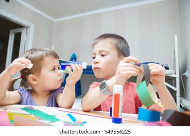 kids development - children making paper colored garland with glue on table, siblings craft, brother and sister playing together