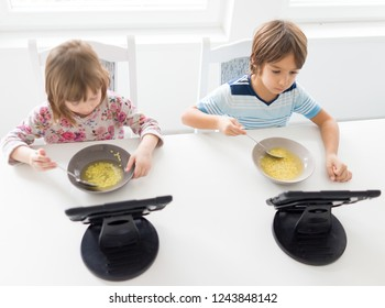 Kids in dining room eating and watching tablet