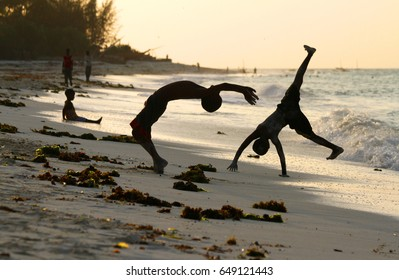 Kids doing backflips and sports on a beach during sunset in Stone Town, Zanzibar, Tanzania