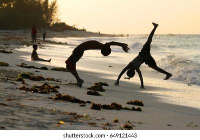 Kids doing backflips and sports on a beach during sunset in Stone Town, Zanzibar, Tanzania
