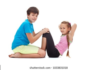 Kids doing gymnastic exercises - helping each other strengthening their abdomens with sit ups