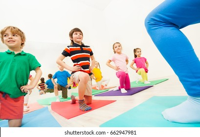 Kids doing knee bending exercises at gym lesson