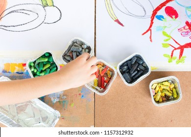 Kids drawing with colorful wax crayons on white paper Wooden background Supplies tools table top view flat lay