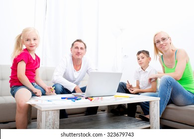 Kids drawing with happy parents on the couch