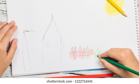Kids drawing and lots of pencils for drawing on wooden background