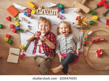 Kids drawing on floor on paper. Preschool boy and girl play on floor with educational toys - blocks, train, railroad, plane. Toys for preschool and kindergarten. Children at home or daycare. Top view