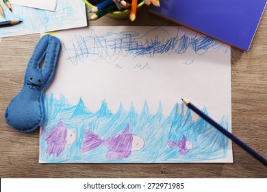 Kids drawing on white sheet of paper with crayons on wooden table, top view