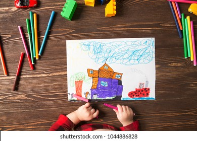 Kids drawing and a lot of painting tools  on a wooden background - Shutterstock ID 1044886828