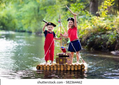 Kids dressed in pirate costumes and hats with treasure chest, spyglasses, and swords playing on wooden raft sailing in a river on hot summer day. Pirates role game for children. Water fun for family