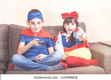 Kids dressed up as super heroes and fantasy characters watching TV