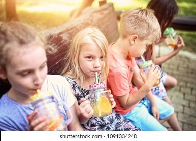 kids drink lemonade on a sunny day