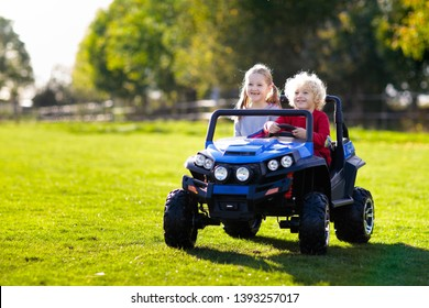 Kids driving electric toy car in summer park. Outdoor toys. Children in battery power vehicle. Little boy and girl riding toy truck in the garden. Family playing in the backyard.
