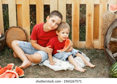 Kids eat fruit outdoors. Healthy snack. Happy family eating watermelon in the garden. Two little cute boys enjoying watermelon. Children having picnic in summer. Children play and eat watermelon.