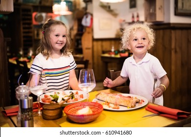 Kids eat pizza, pasta and salad in traditional restaurant.  Eating out with children. Boy and girl having dinner in pizzeria in Italy on vacation in Europe. Italian food and cuisine for family