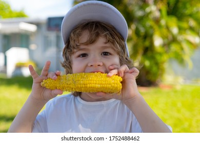 Kids eating corn. Food for kids. Cute boy eating healthy food in nature background