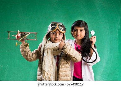Kids and education concept - Small indian boy and girl posing in front of Green chalk board in pilot fancy dress and doctor costume with stethoscope