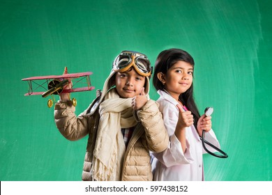 Kids and education concept - Small indian boy and girl posing in front of Green chalk board in pilot fancy dress and doctor costume with stethoscope, standing over green chalkboard background