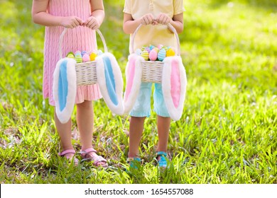 Kids with eggs basket and bunny ears on Easter egg hunt in sunny spring garden. Little boy and girl searching for colorful candy and chocolate eggs with rabbit basket. Children celebrating Easter.