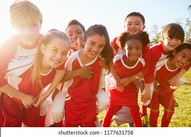 Kids in elementary school sports team piggybacking outdoors