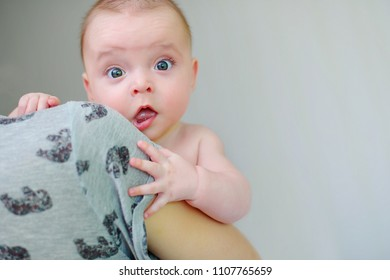 Kids emotions, surprised baby on his mother's arms, child's eyes widened and mouth opened in amazement. copy space for your text