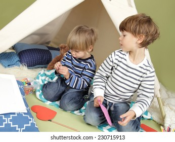 Kids engaged in arts and crafts activity, playing in a teepee tent at home