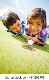 Kids enjoying playing golf lying on the field and smiling