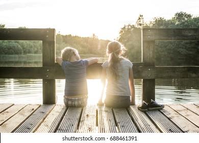 Kids enjoying summer at the lake sitting on the dock