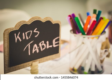 Kids entertainment table at a wedding with colorful markers in a jar and a chalkboard sign