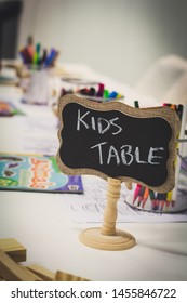 Kids entertainment table at a wedding with colorful markers in a jar and paper with a chalkboard sign
