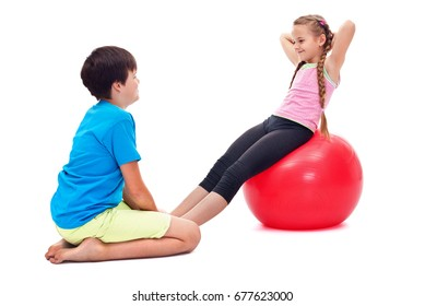 Kids exercising together strengthening abdomen muscles - using a large rubber gymnastic ball