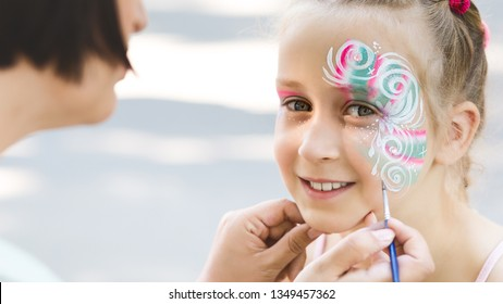 Kids face painting. Adorable little girl getting creative pattern on her face, free space