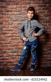 Kid's fashion. Modern nine year old boy posing at studio over brick wall background. Clothes and accessories for children.