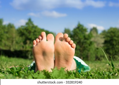 Kid's feet close up, the child is lying on green grass in the park on a sunny day.