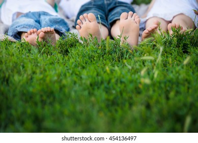 Kids feet lying on green grass in sunny day. Concept happy childhood.