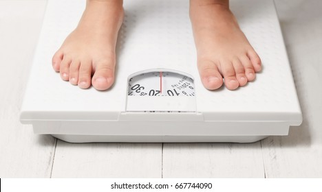 kids feet stand on white weight scale