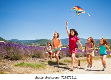 Kids flying kite running through lavender field