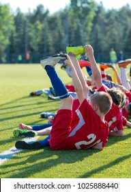 kids football players do their stretching exercises after good training on the field