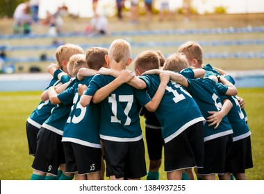 Kids football team building team spirit. Soccer children team in huddle. Group of boys united before the final soccer match