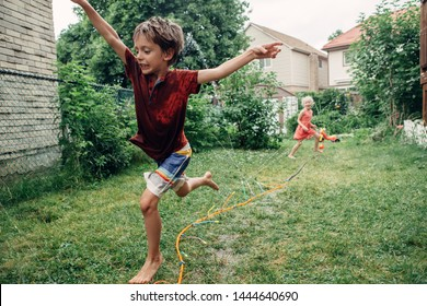Kids friends boy girl splashing with gardening hose sprinkler on backyard on summer day. Children playing with water outside at home yard. Candid authentic real life moment of funny family activity
