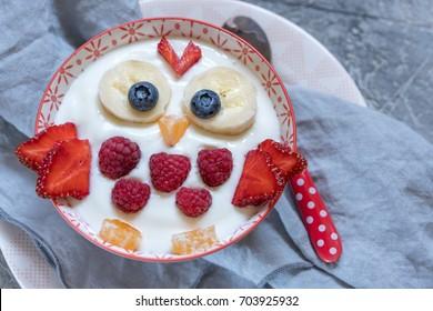 Kids funny breakfast yogurt with fruits and berries