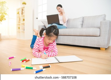 kids girl lying down on wooden floor drawing on sketchbook and mother working with computer talking on the phone on background in the living room at home. family activity concept