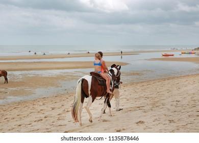 Kids girl rides on horse at beach. Huahin thailand.