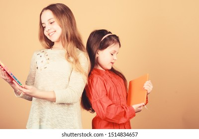 Kids girls with books or notepads. Education and kids literature. Favorite fairytale. Sisters pick books to read together. Adorable girls love books. Secret diary or personal journal. Smart is great.