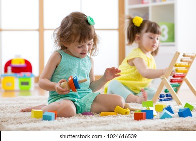Kids girls are engaging in daycare. Two toddler children playing with educational toys in kindergarten.
