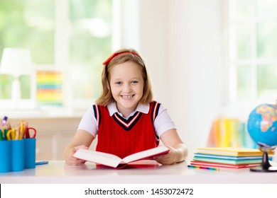 Kids go back to school. Children study and learn for preschool. Little girl of elementary class doing homework. Bedroom with desk, books and globe for young child. Kid learning to read and write.