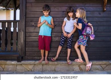 Kids gossiping. Girl whispering something to other girl, boy eavesdropping. Kids playing, playfulness.