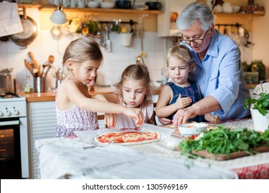 Kids and grandmother cooking italian pizza in cozy home kitchen for family dinner. Cute girls are preparing homemade food. Old senior woman is teaching three little sisters. Children chef concept.