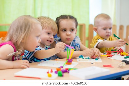 Kids group making arts and crafts in kindergarten. Children spending time in day care centre with the great interest.