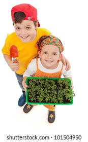 Kids growing food - holding spring seedlings and gardening tools, isolated
